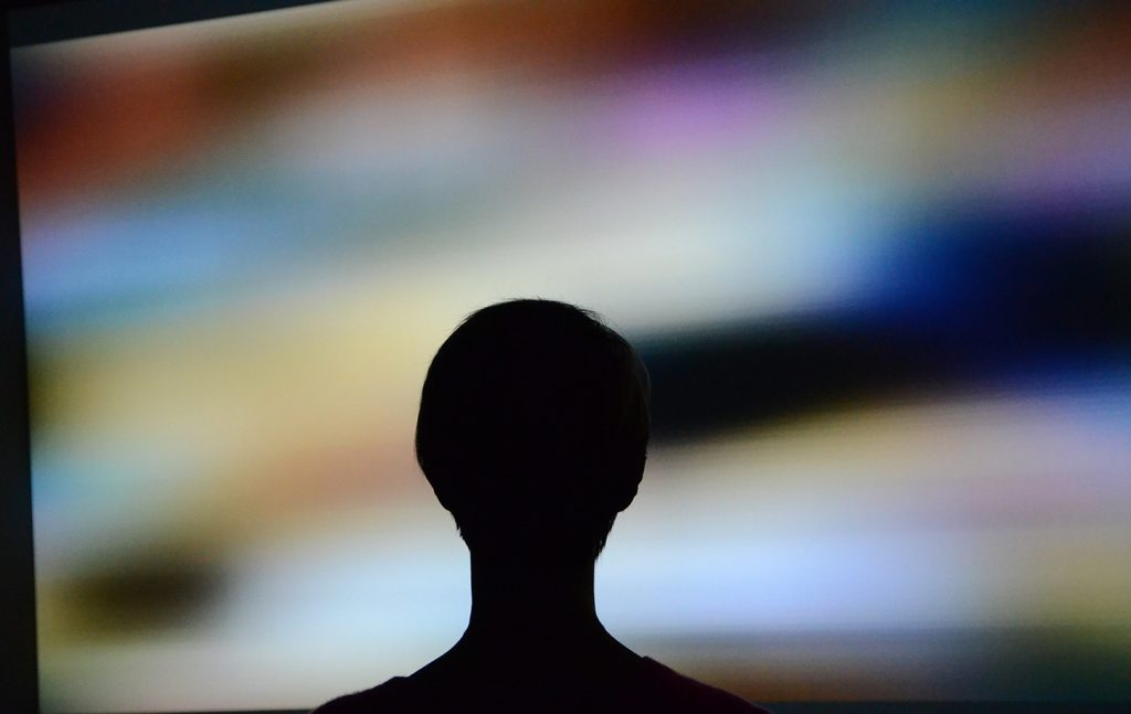 Silhouette of viewer in front of Signals and Stillness projected display.